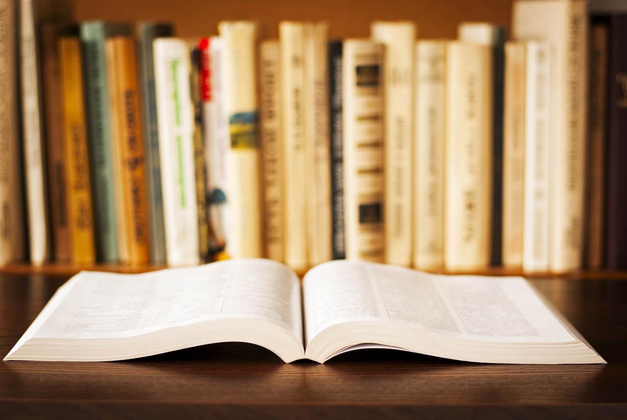 zdjęcie rozłożonej książki na stole, w tle regał z książkami