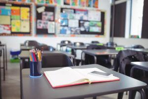 zdjęcie klasy, na pierwszym planie ławka szkolna z rozłożonym zeszytem, obok telefon i kubek z kredkami