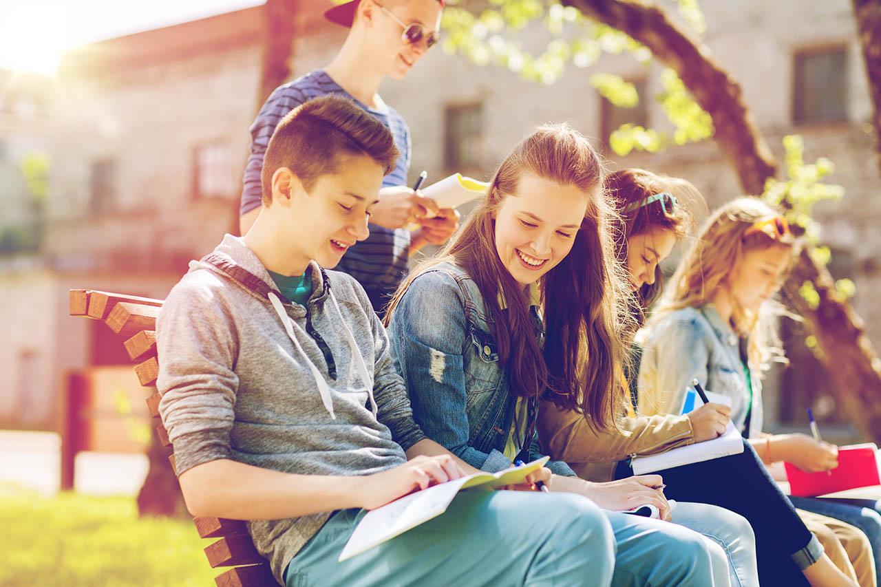 grupa młodzieży siedząca na ławce