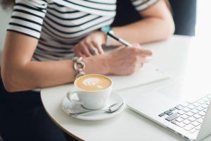zdjęcie osoby piszącej w notatniku przed otwartym laptopem, z boku filiżanka kawy