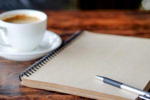 zdjęcie przedstawiające filiżankę kawy na spodku, obok notatnik z długopisem