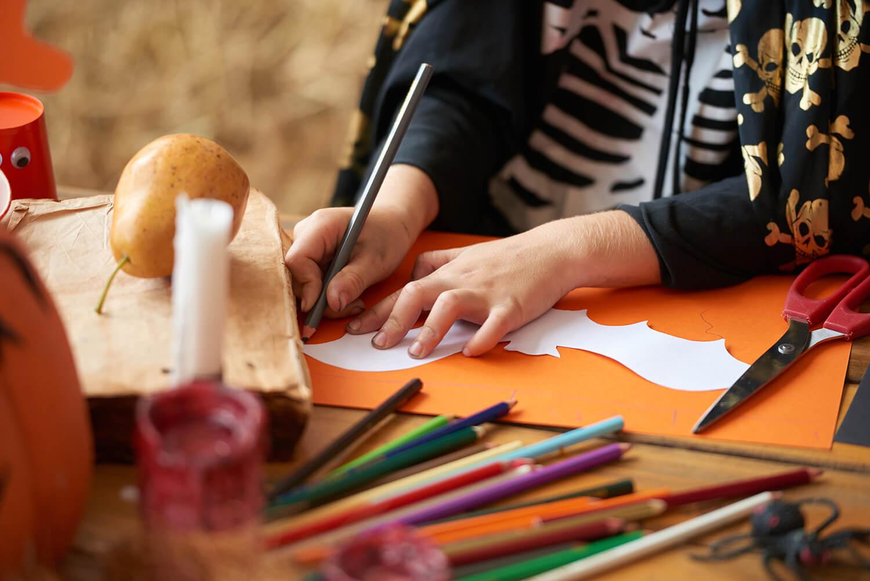 zdjęcie rąk odrysowujących papierowy wzór nietoperza